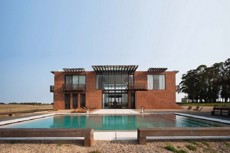 A villa with a bold brick facade and warm contemporary interior