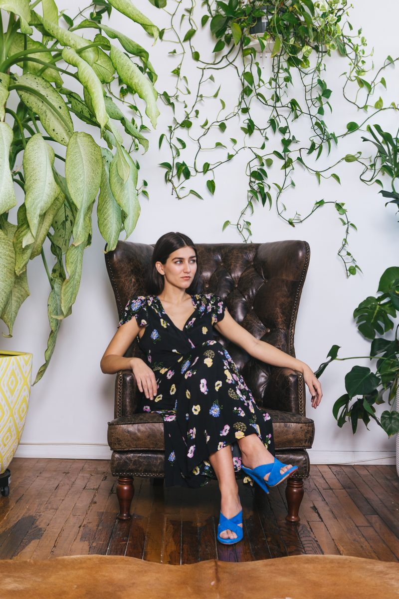 woman in black and white floral dress sitting on brown couch