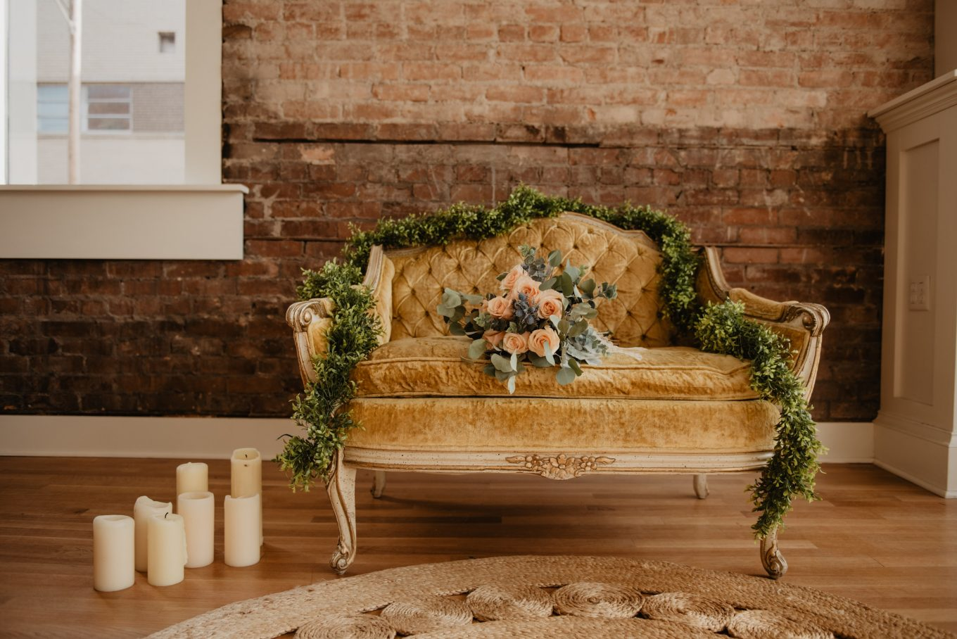 vacant tufted beige loveseat with bouquet of orange rose flowers