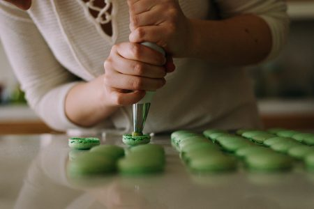 selective focus photography of woman putting icing on cupcakes