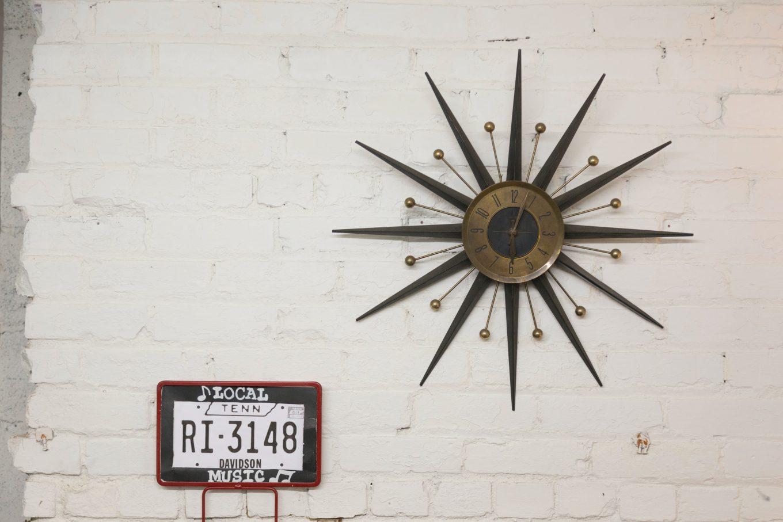 brown and black sun designed analog wall clock at 6:05