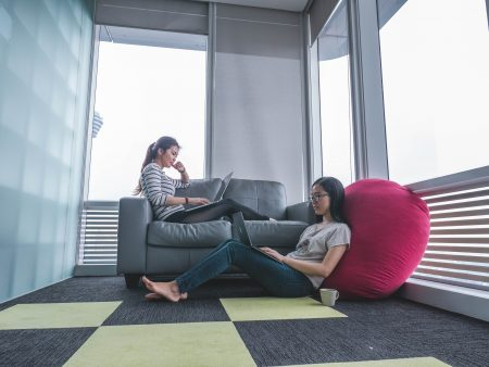 two women sitting on sofa and floor inside gray painted room