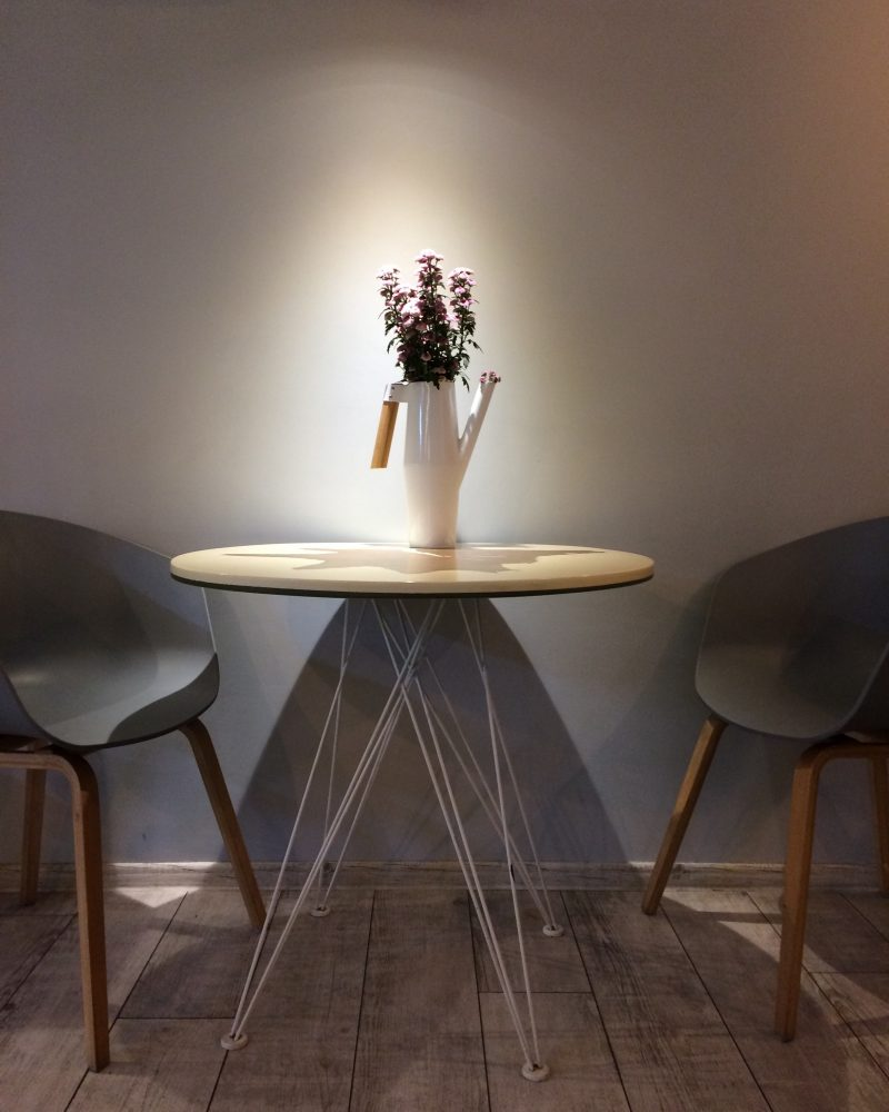 brown wooden round table with white ceramic vase