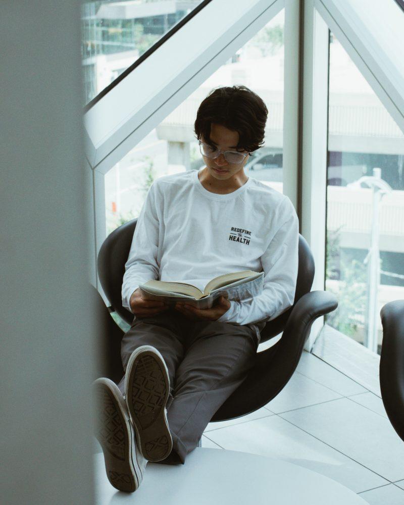 man in white crew neck t-shirt sitting on black armchair