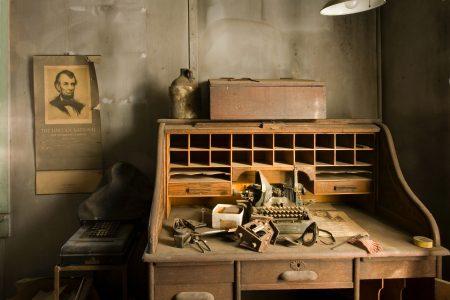 brown wooden desk with typewriter