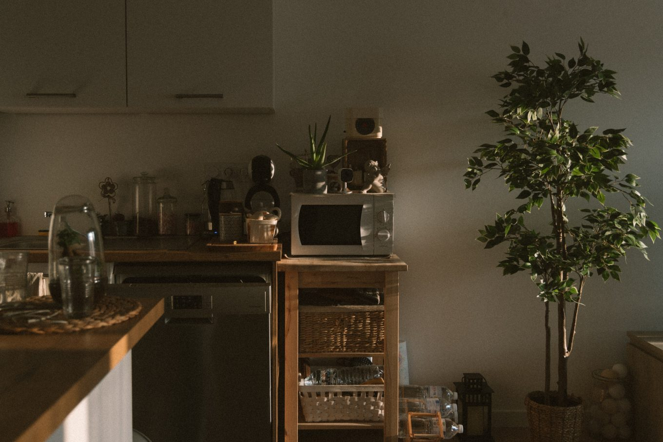 silver microwave oven on brown wooden kitchen cabinet