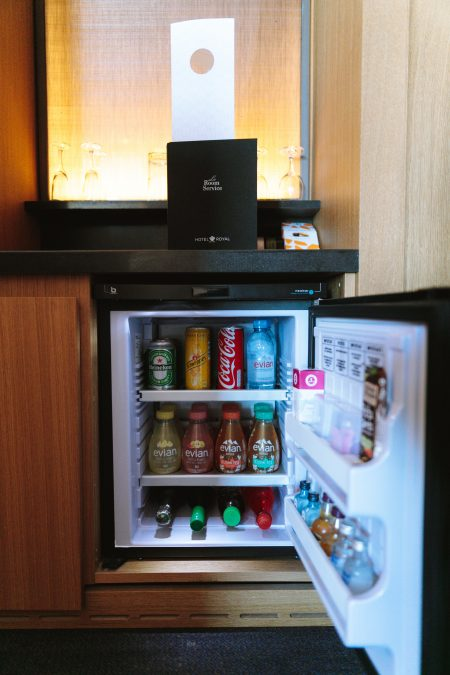 open black compact refrigerator filled with soda bottles