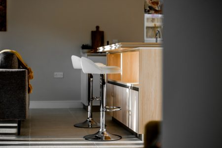 shallow focus photo of white hydraulic bar chairs