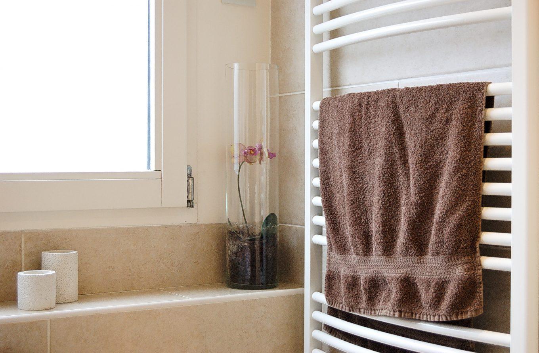 pink towel on white metal rack
