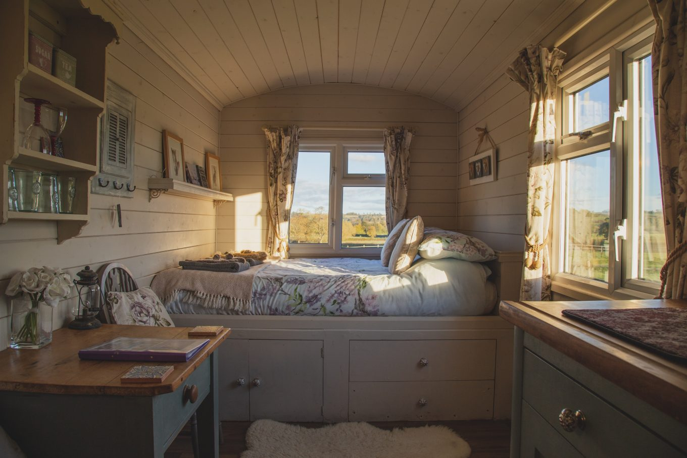 empty bed beside windows during daytime