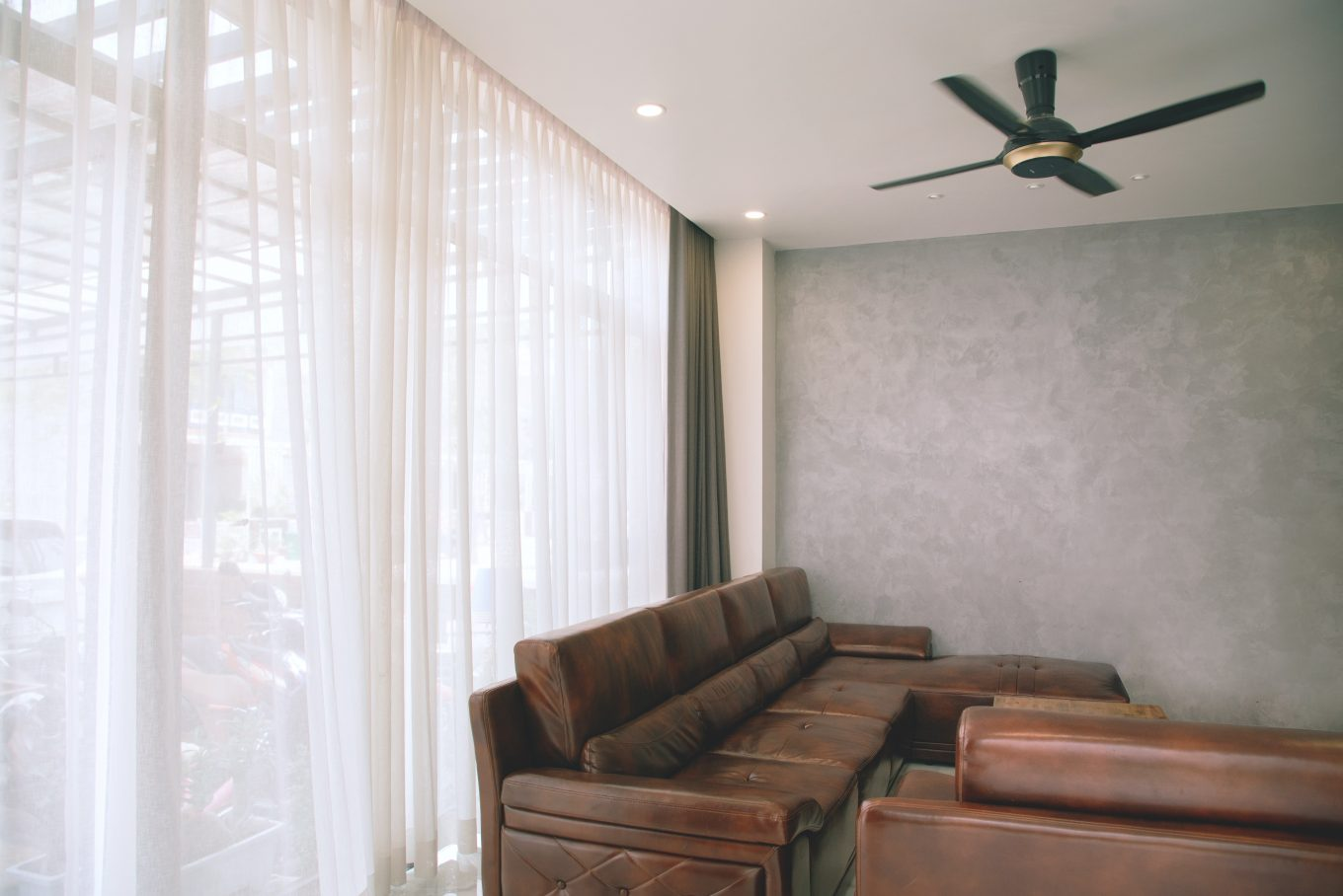 brown couch and black celing fan