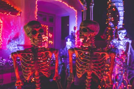 two skeleton near white concrete building with string lights at daytime